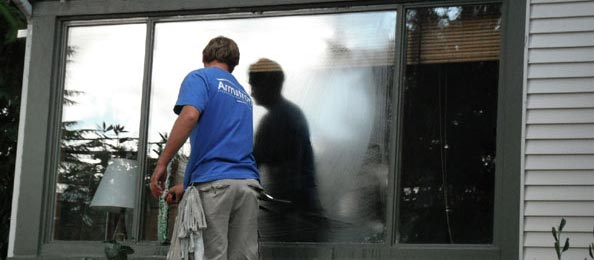 An armstrong employee cleaning a window.