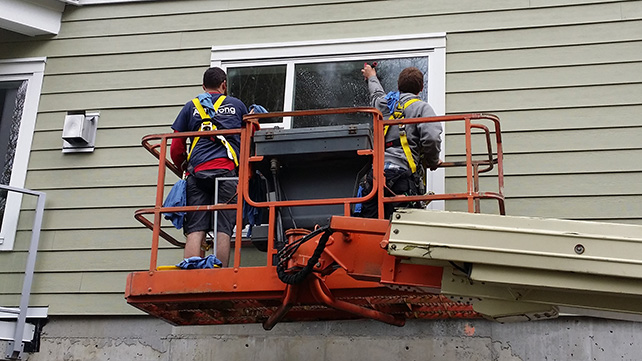 Two men on a hydraulic lift cleaning windows.